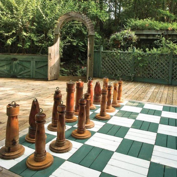Chess board painted on wood patio deck. Each figure has a circular handle.