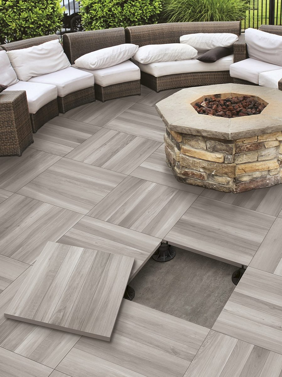 Elevated Patio Tile Floor By Serenissima With A Fire Pit Installed On It