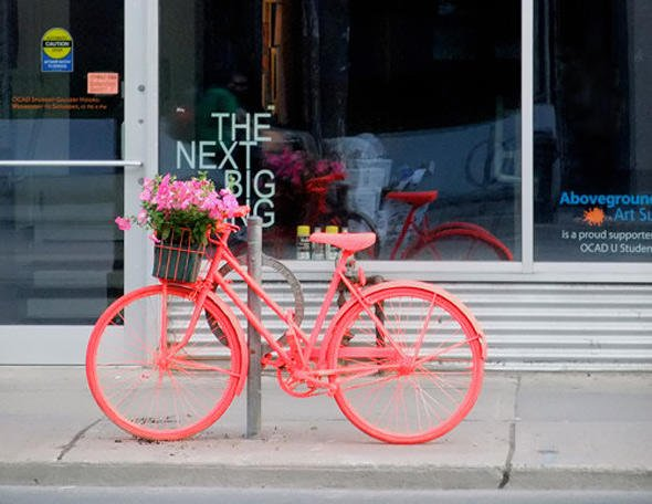 Pink painted Bicycle planter on the street