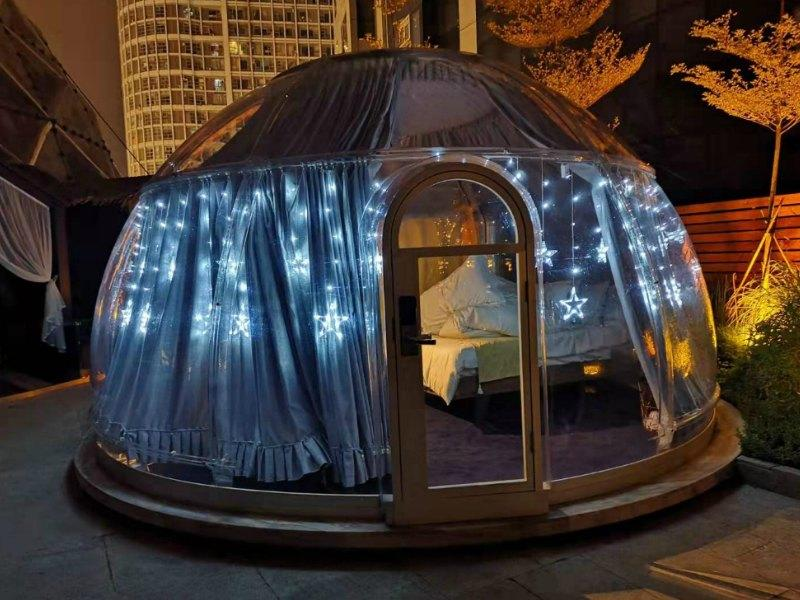 A transparent dome at night - with curtains and fairy lights.