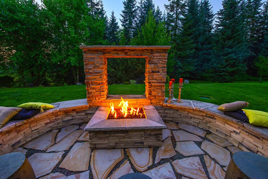 Amazing colorful flagstone patio design with a fire pit and seating arrangement