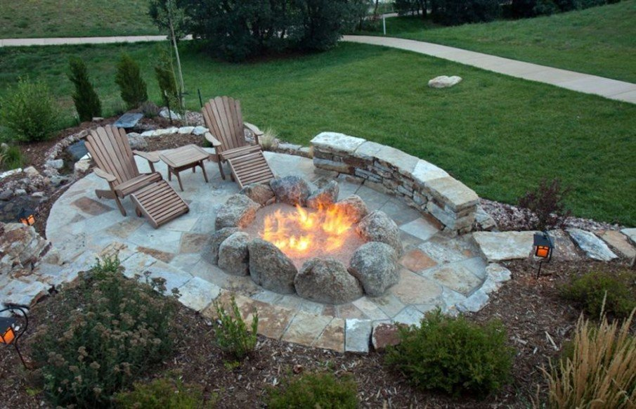 Amazing DIY flagstone patio with stone clad fire pit and patio lounge chairs