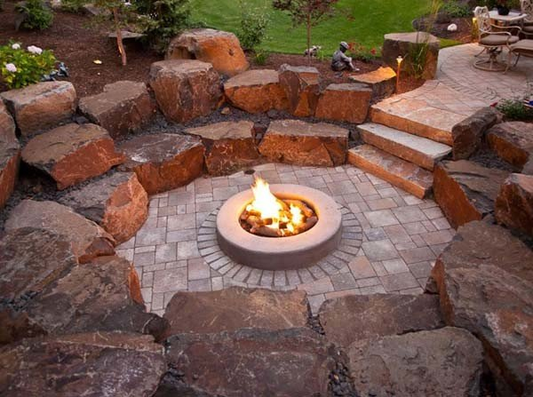 Beautiful sunken patio with fire pit made with oversized landscaping stones
