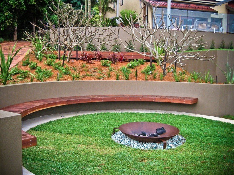 Built in wooden fire pit seating on circular patio