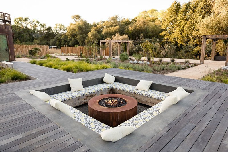 Concrete square patio with firepit sunken into wood deck
