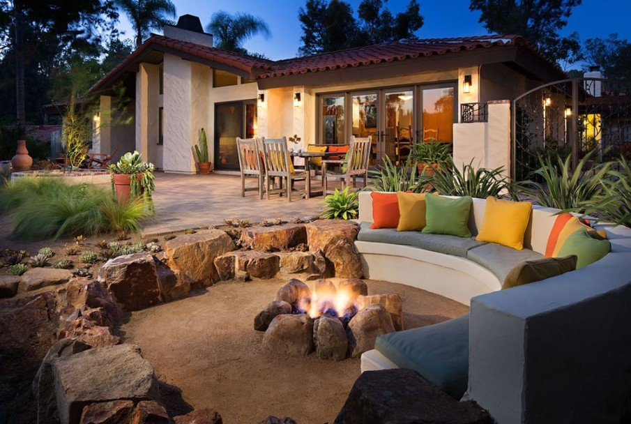 Cozy patio with sunken stone fire pit and concrete seating