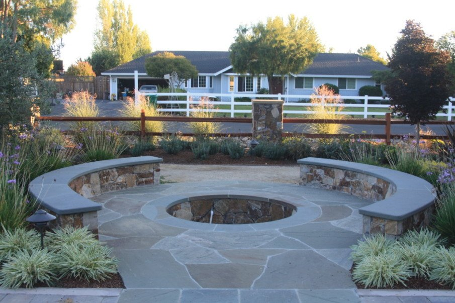 An elegant flagstone patio design with fire pit in the center