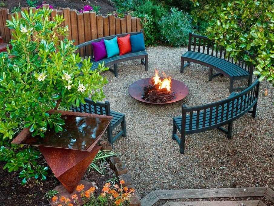 Circular benches with colorful cushions around a fire place