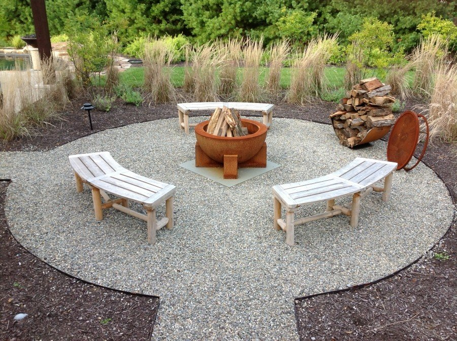 Circular pebble patio with benches and a metal fire pit idea