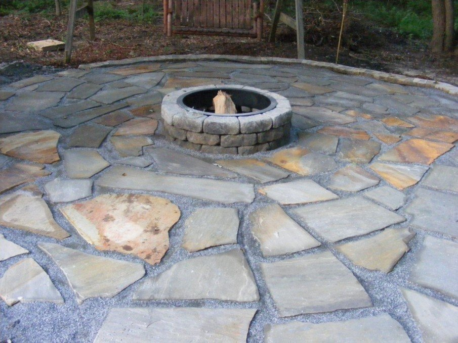 A flagstone patio with central brick fire pit