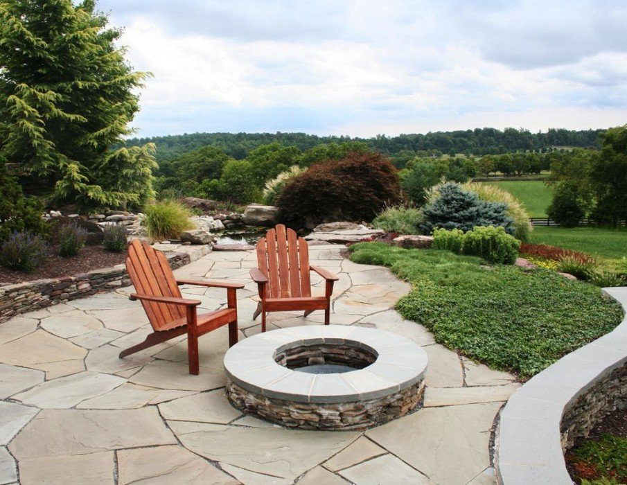A hardscape patio design with flagstone fire pit