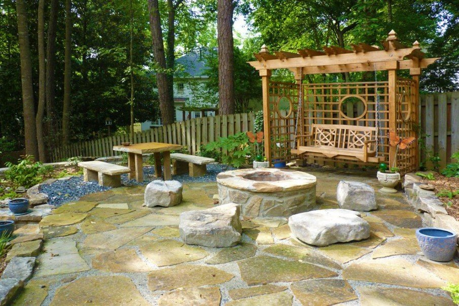 A hardscape patio design with pergola swing and flagstone firepit