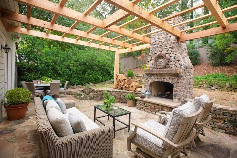 Large patio with simple pergola and rustic fireplace
