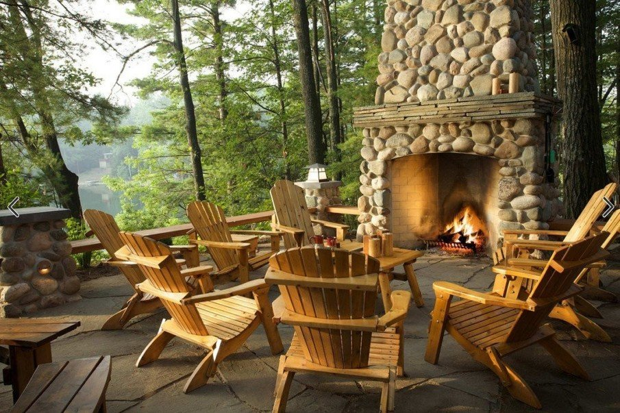 Log home style outdoor fireplace on flagstone patio