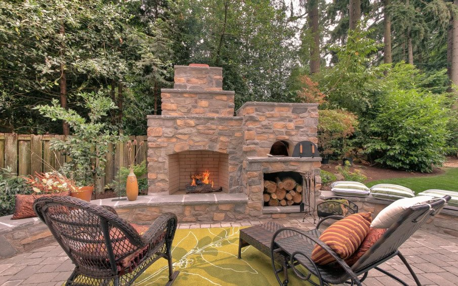 Patio fireplace idea with outdoor rug and pizza oven