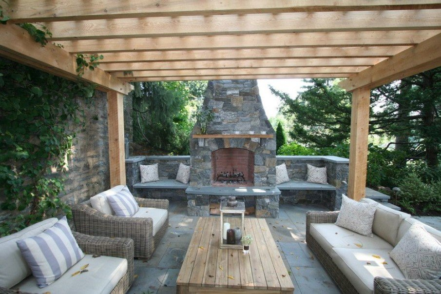 Patio with wood pergola design and stone fireplace