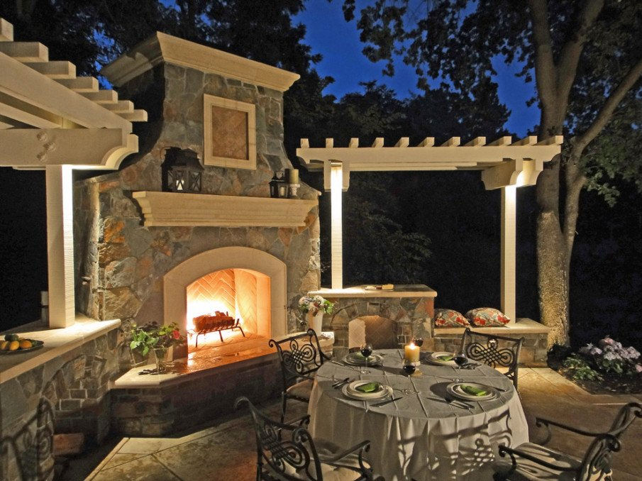 Patio with two decorative pergolas and a fireplace