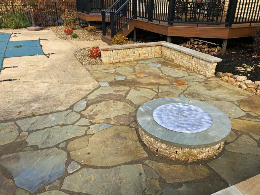 A poolside flagstone patio with fire pit