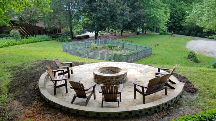 Raised circular patio design with fire pit in the middle