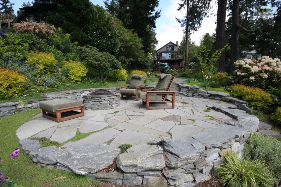 Raised flagstone patio idea with a fire pit on the side