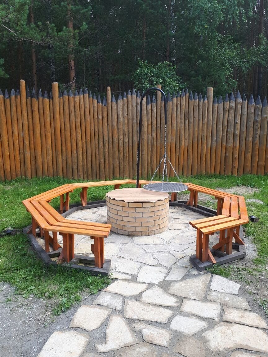 Round flagstone fire pit patio with circular wood seating