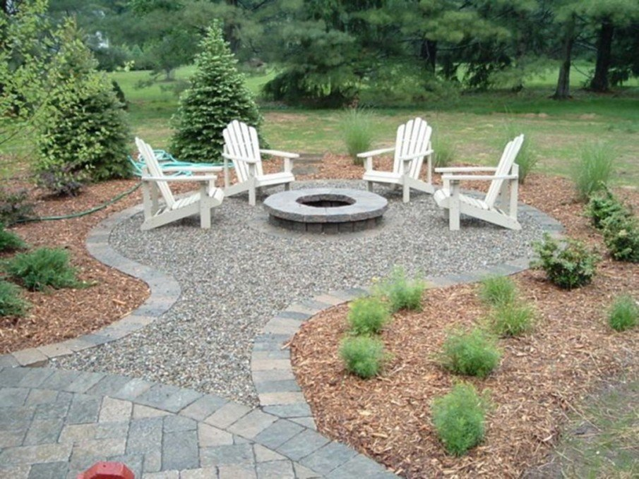 Simple cement block and gravel fire pit setting with white chairs