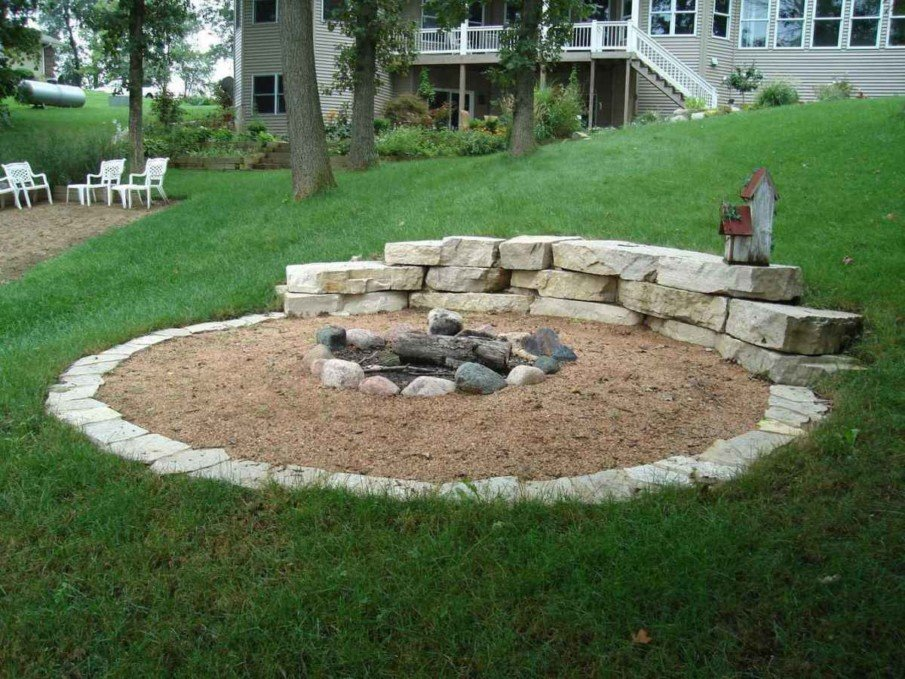 Lay some landscaping stones right on sand to build a simple fire pit seating