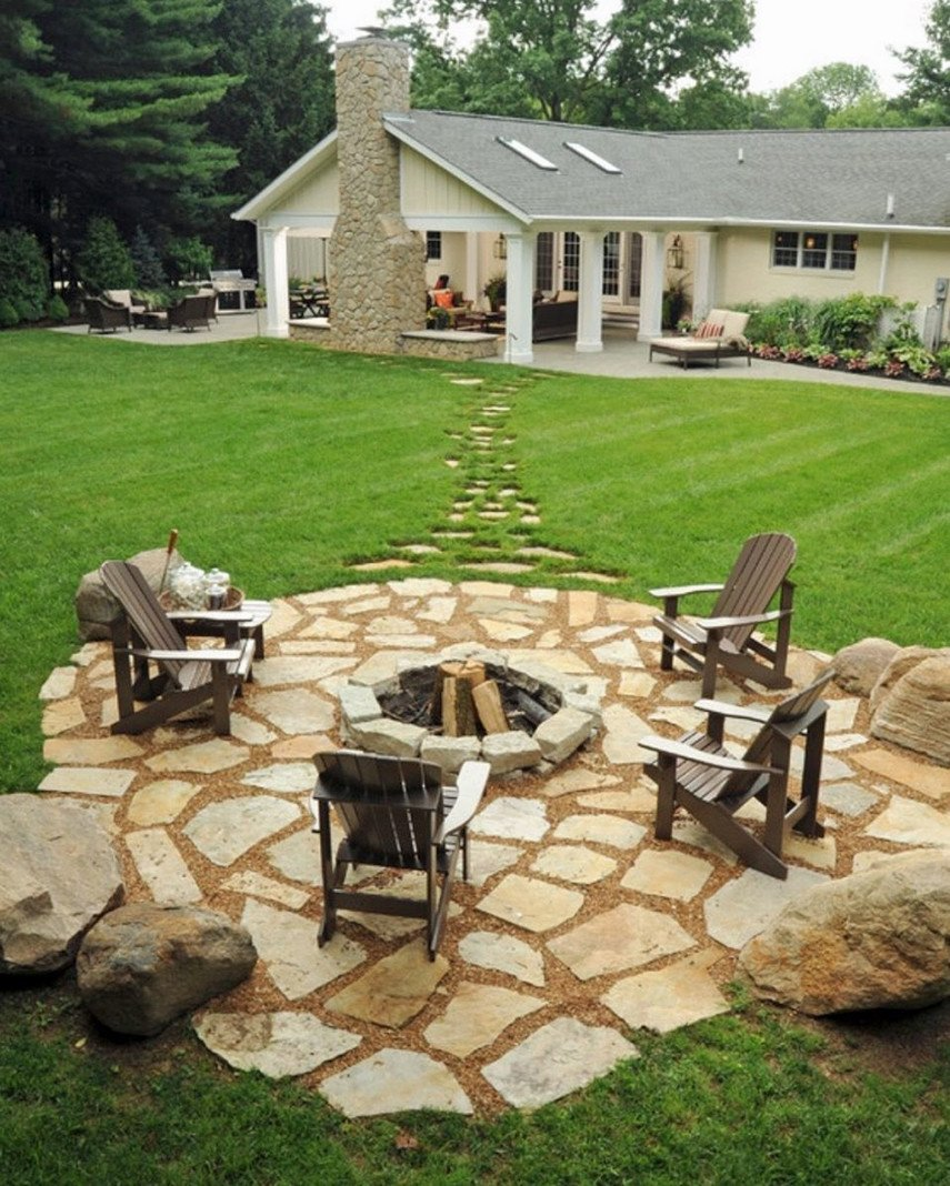 Simple flagstone patio design with fire pit and wooden chairs