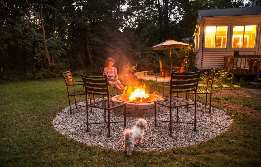Simple gravel fire pit setting with steel chairs