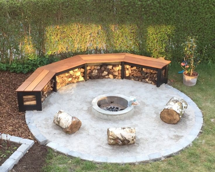 Small concrete patio with fire pit and a semi circular wooden bench