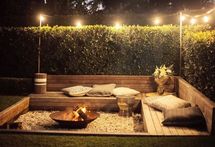 Small sunken patio with metal fire pit and wood seating