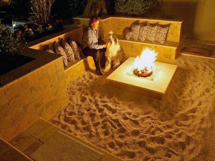 Small sunken patio with sand floor and square firepit