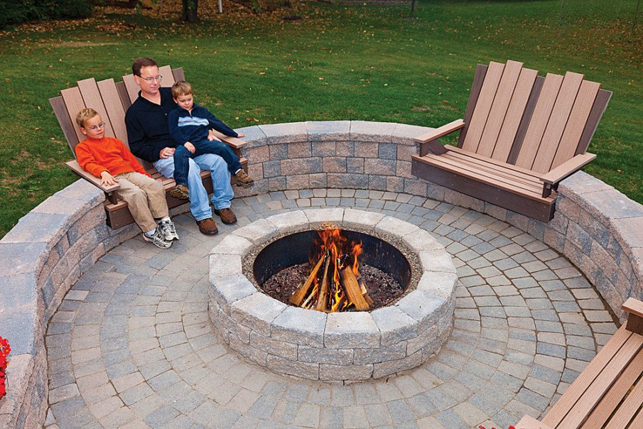 Stone circular fire pit area design with built in wood seats
