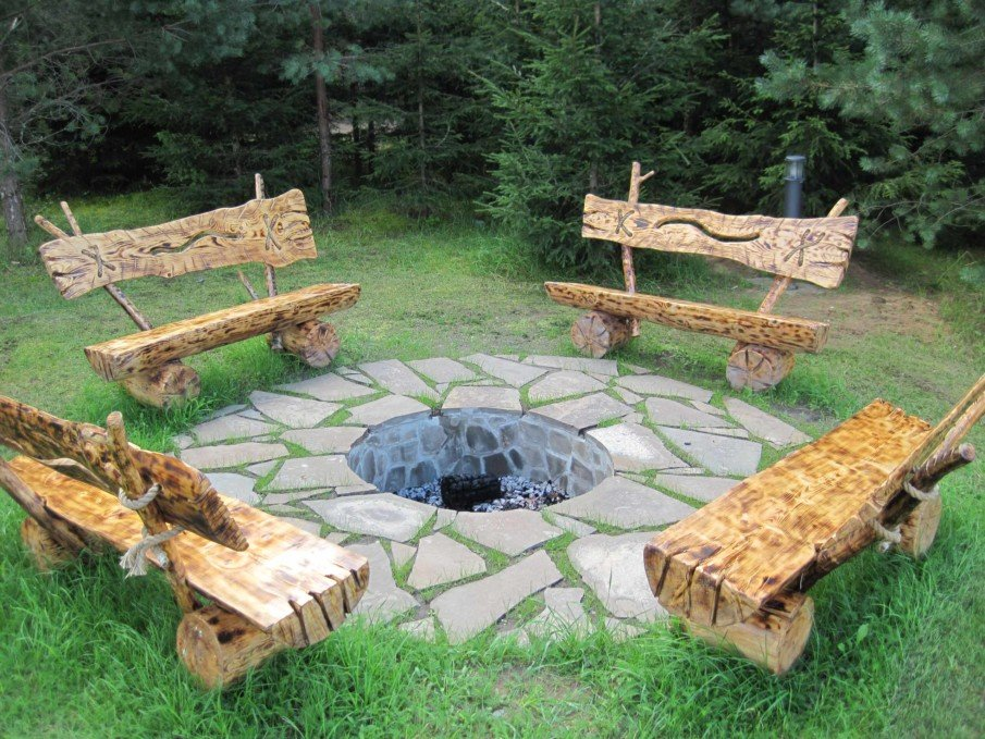 Rustic sunken fire pit surrounded by diy artistic wooden benches