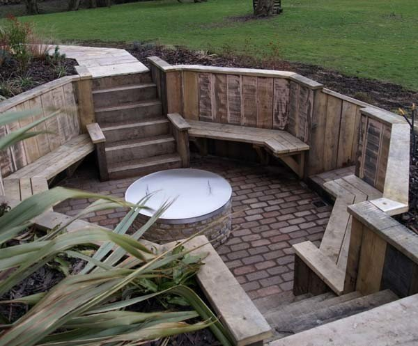 Sunken brick patio with round fire pit and wood seating idea