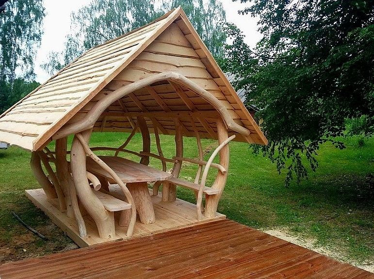 Unique backyard structure with a roof and two benches
