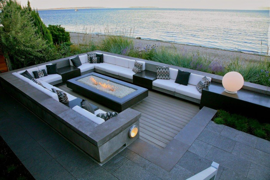 Waterfront patio seating area with sunken fireplace