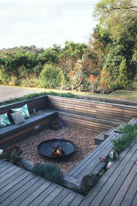 Wood deck with small sunken fire pit setting on gravel floor