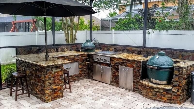 Built-in big green egg grill in stone tile outdoor kitchen