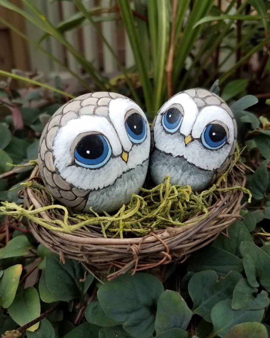 Two owl painted pebbles in a nest