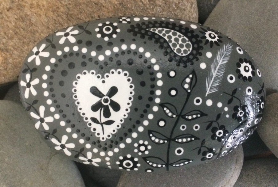 Beautiful floral black and white painting on a rock
