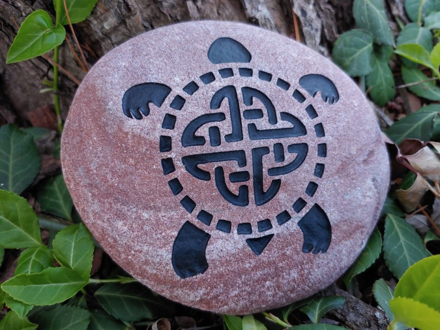 A tortoise engraving on a round river rock