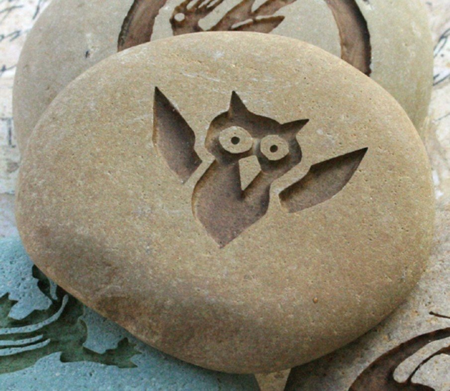 A baby owl engraved on a pebble