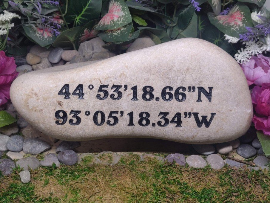 Longitude and Latitude coordinates engraved on an oversized garden river rock