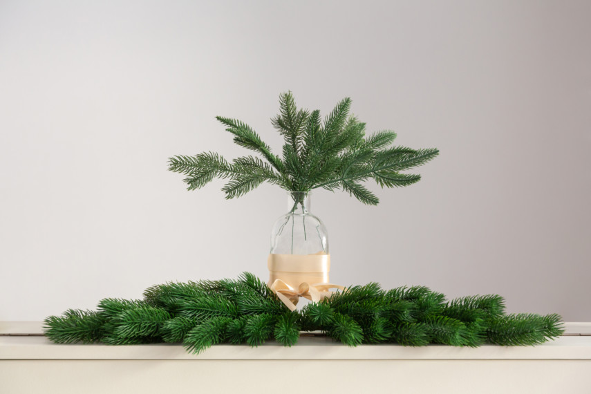 Glass bottle with spruce boughs centerpiece