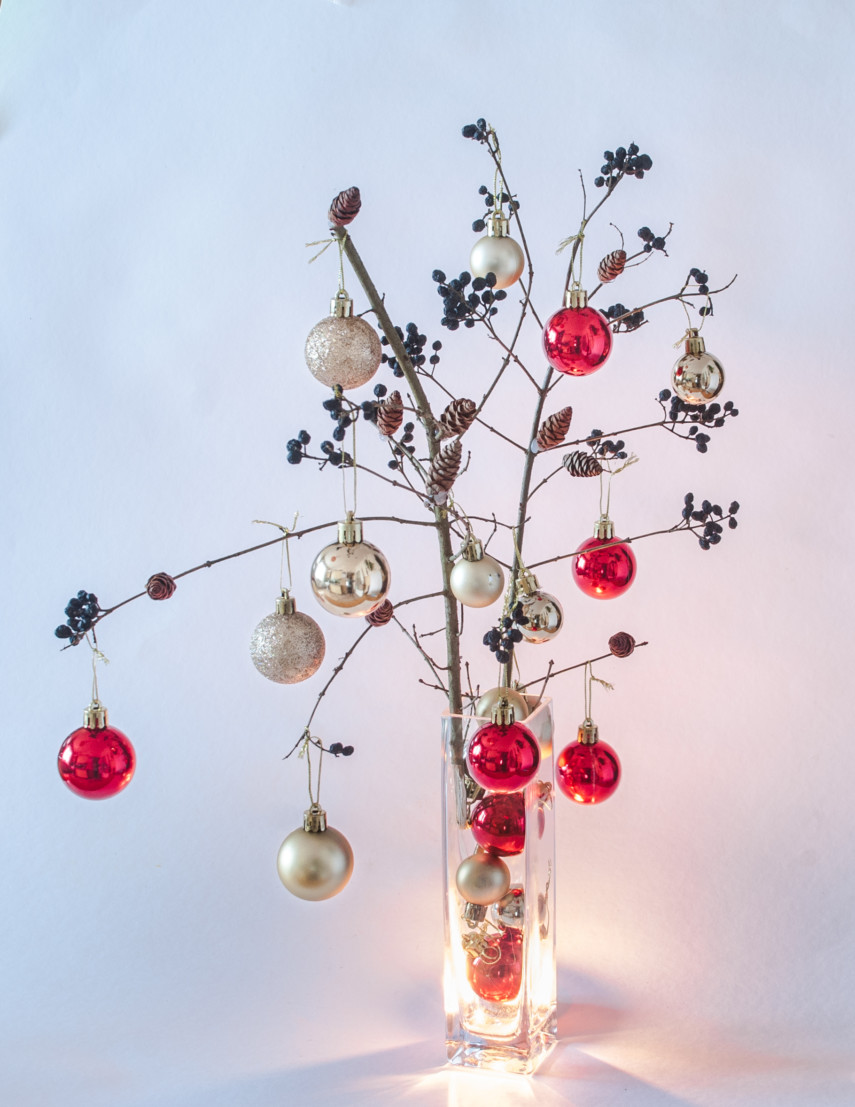 Crhistmas ball ornaments decorate twigs in tall square vase