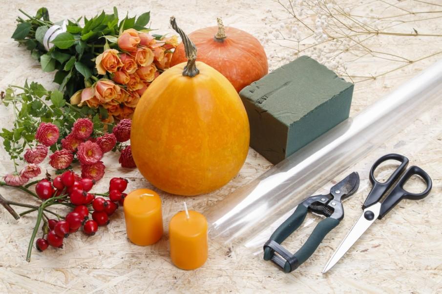 Making pumpkin centerpiece using yellow pumpkin, a bouquet of flowers and cranberries