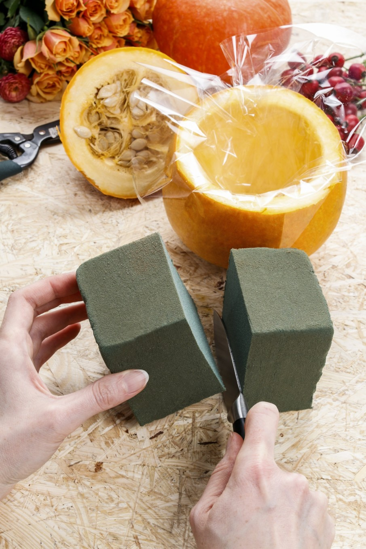 Cut the floral foam block to fit the pumpkin