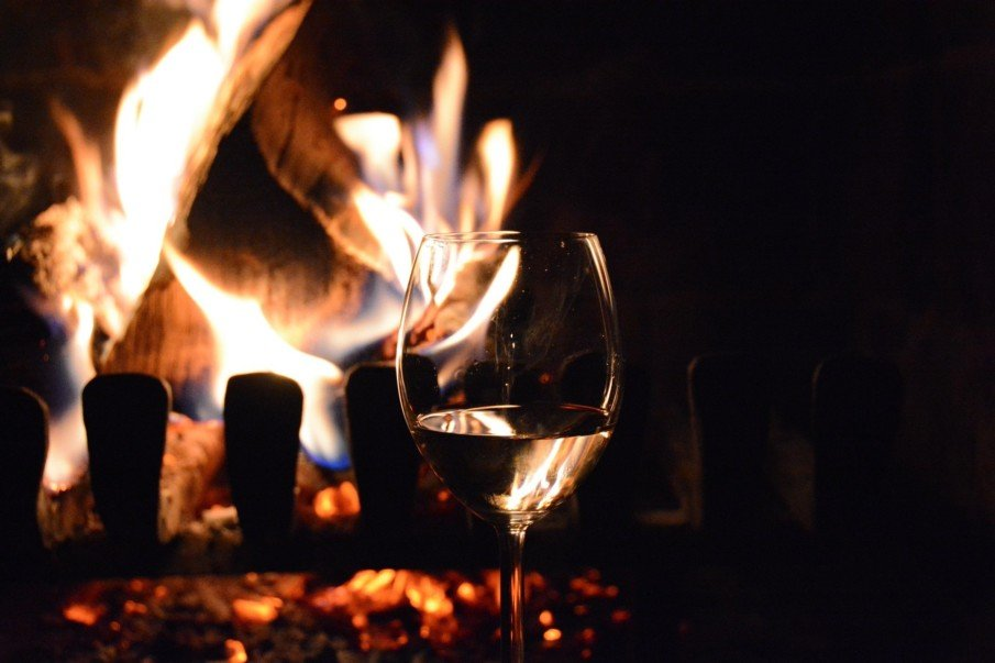 Glass of wine in front of roaring fireplace
