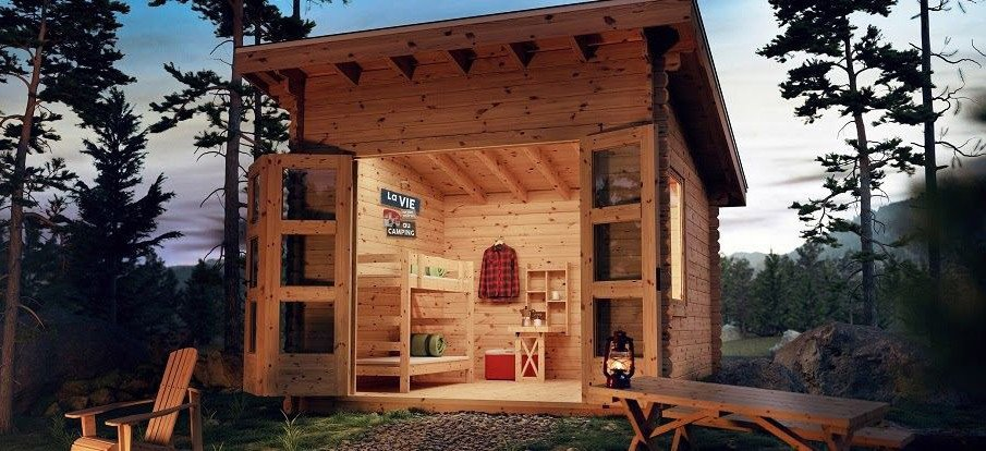 A rustic outdoor bunkie is built near a mountain trail